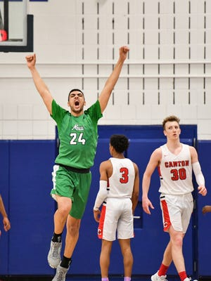 Novi's Tariq Woody (24) celebrates his game-winning tip-in at the buzzer to beat Canton, 60-58.