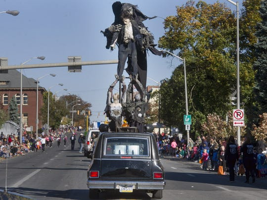 A Field of Screams hearse has monsters fly out of the roof during the 2014 York Halloween Parade.