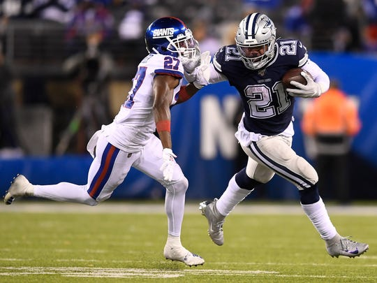 EAST RUTHERFORD, NEW JERSEY - NOVEMBER 04: Ezekiel Elliott #21 of the Dallas Cowboys carries the ball as Deandre Baker #27 of the New York Giants defends during the fourth quarter of the game at MetLife Stadium on November 04, 2019 in East Rutherford, New Jersey. (Photo by Sarah Stier/Getty Images)