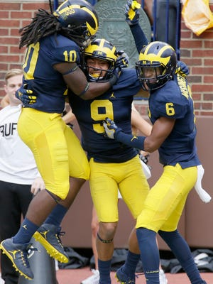 Michigan Wolverines' Grant Perry (No. 9) celebrates with Devin Bush, left,  and Keith Washington after returning a blocked punt for a TD against Colorado on Sept. 17, 2016 in Ann Arbor, Michigan.