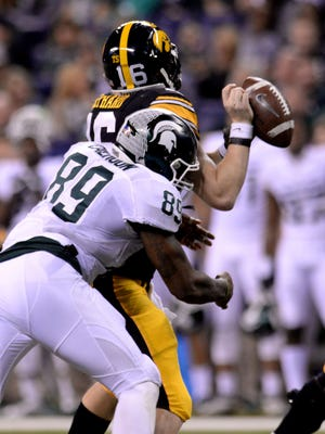 Defensive end Shilique Calhoun make Iowa quarterback C.J. Beathard drop the ball as he hits him in the first half December, 5, 2015, in Indianapolis at the Big Ten Championship football game. Iowa would recover the fumble.