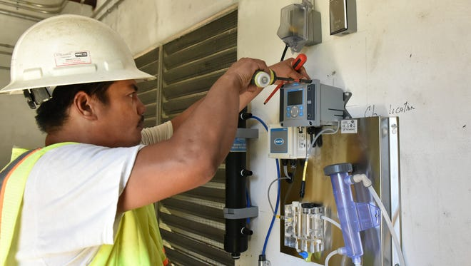 Kinden Corp. electrician Hart Lacanilao installs a water analyzer at Guam Waterworks Authority's A-25 water well along Route 4 in HagŒt–a on June 9, 2017.