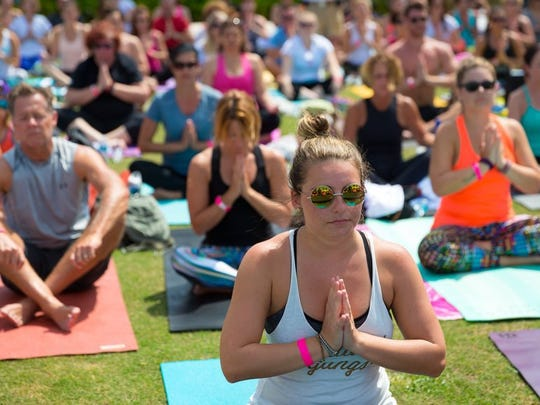 "Attendees, including Naples resident Katrina Drescher, center, chant ""Om"" while finishing a yoga workout the third annual YogaCAN event at the Naples Beach Hotel & Golf Club on Sunday, April 3, 2016, in Naples. Instructors from three local yoga studios led over 300 people in yoga workouts at the annual event with proceeds benefitting the Cancer Alliance of Naples. (David Albers/Staff)"