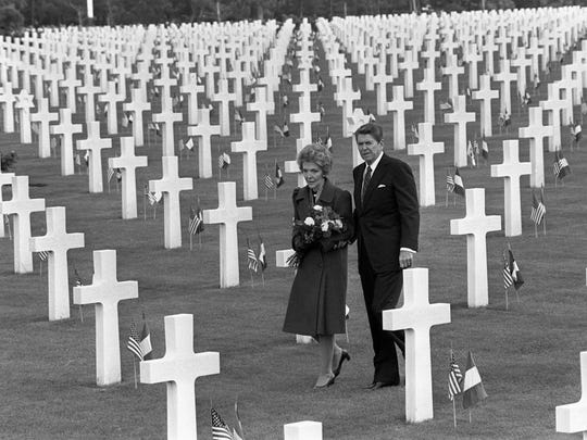 Former U.S. President Ronald Reagan and former first lady Nancy Reagan walk through the thousands of graves in the American Cemetery in Omaha Beach, Normandy, France, in this June 6, 1984 file photo, during ceremonies for the 40th anniversary of the D-Day allied invasion of occupied France.