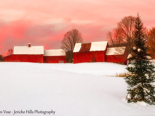 A winter scene of a red barn, snow and a pink sky at sunset taken in Quechee.