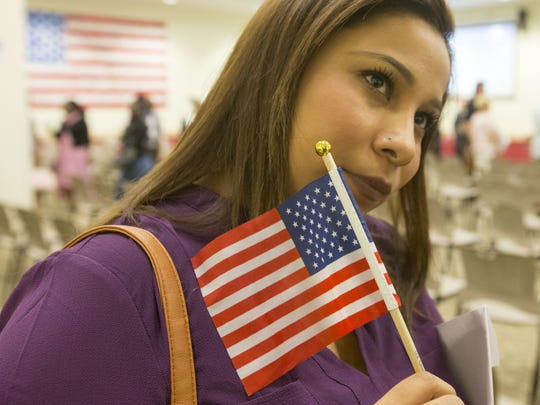 New citizen Elizeth Ramirez Reynaga from Mexico rejoices to become a new citizen of the U.S. reacts to a new video message welcoming citizens recorded by President Trump at the U.S. Citizenship and Immigration Services office in Phoenix on Tuesday, Oct. 24, 2017.