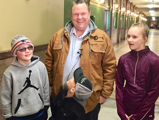Sen. Jon Tester fields questions Tuesday from reporters as his grandchildren, from left, Brayden, Tucker and Kilikina Schultz look on.