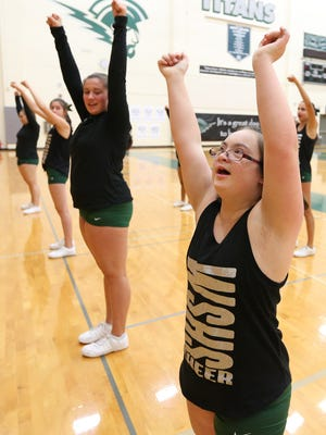 Lora Harrington, center, who has Down Syndrome, and the West Salem High School Junior Varsity cheerleading squad practice on Monday, Oct. 17, 2016, at the school.