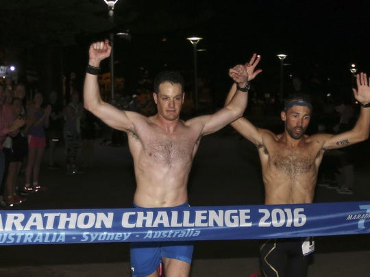 Daniel Cartica, left, and Calum Ramm, both from the United States, cross the finish line in the seventh and final leg of the World Marathon Challenge, Saturday, Jan. 30, 2016, in Sydney, Australia. Cartica, from Poughkeepsie, N.Y, and Becca Pizzi, from Belmont, Mass., won the World Marathon Challenge, completing seven marathons in seven days on all seven continents. (AP Photo/Rob Griffith)