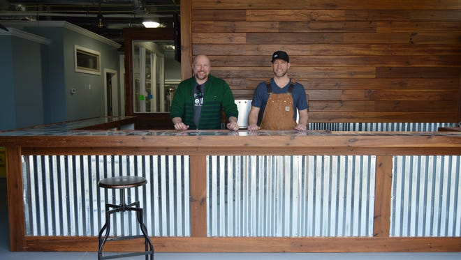 Harry Metcalfe and Patrick Staggs of Revelation Brewing Company smile behind their microbrewery bar, located in West Rehoboth, on March 23, 2016.