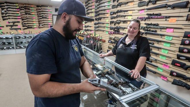 Salesperson Cathy Lewis shows Michael Cordova, of La Quinta a handgun at Second Amendment Sports in Palm Desert on Wednesday, Jan. 3, 2018.