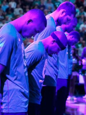 Boston Celtics' Isaiah Thomas, center, and teammates bow their heads during a moment of silence for Thomas' sister Chyna before a first-round NBA playoff game against the Chicago Bulls on Sunday in Boston.
