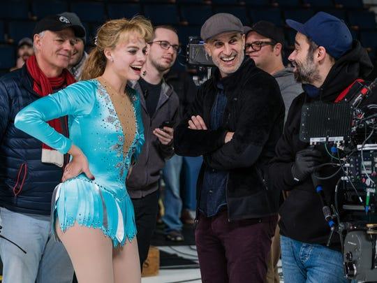 Wearing her figure-skating garb, Margot Robbie watches