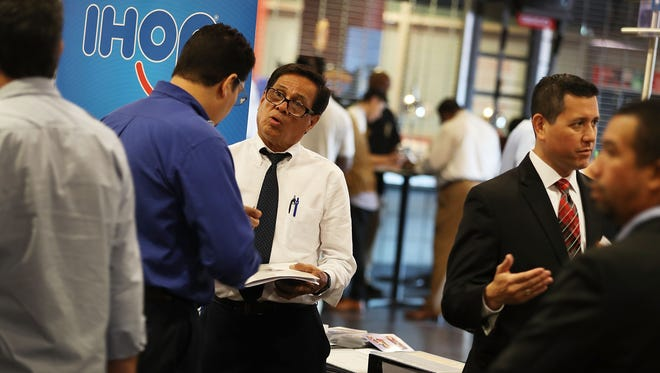Edgar Colomer (L) speaks to a recruiter for IHOP restaurants during the JobNewsUSA job fair at the BB&T Center on November 15, 2016 in Sunrise, Florida.  Over 30 companies were looking to fill approximately 2,000 positions.