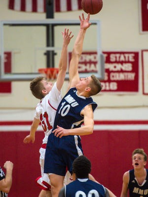 Champlain Valley Union's Walker Storey, left, and Mt. Mansfield Union's Zach Reinhardt contest the tip-off in Hinesburg on Tuesday, December 20, 2016.