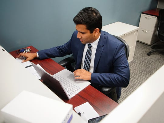 Mohammed Alam, an associate at Swarthmore Financial Services does some client research at his desk.