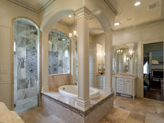The master bathroom at 1063 Southern Trace Parkway features an over-sized shower with four shower heads, marble bench and a  separate throne-like tub.