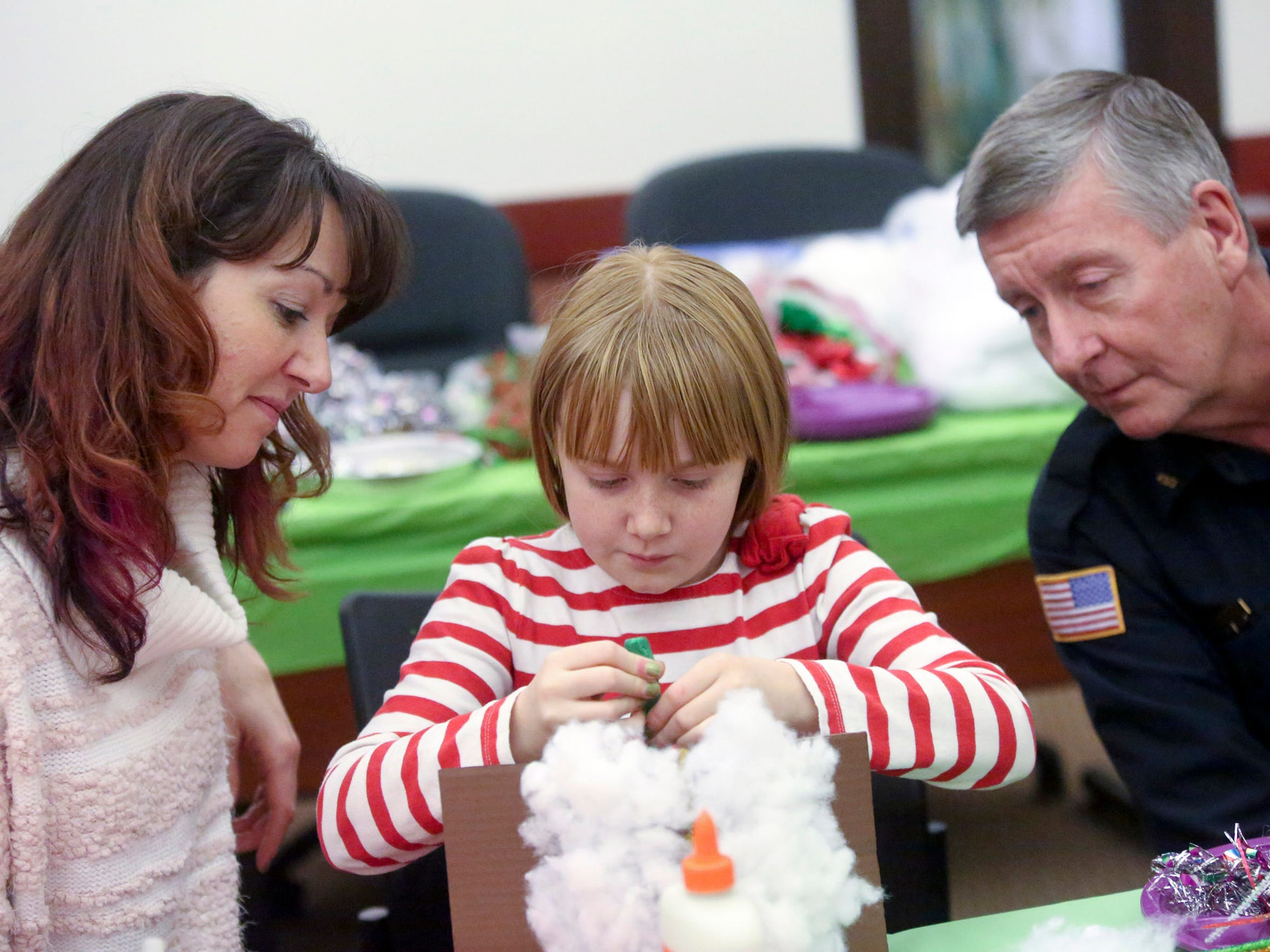 Ava Lenz works on her gingerbread house under the eyes of her mother, Hilary Prokop, and then-Pewaukee Police Chief Tim Otto during a past 12 Days of Christmas. This year's 12 Days event will run from Nov. 29-Dec. 10.