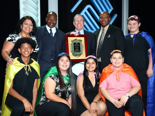 """Champion of Youth Award Back row (Left to Right): Juanita Godwin (Unit Director, Coachella Boys & Girls Club); Quinton Egson, CEO, Boys & Girls Clubs of Coachella Valley; Jim Ducatte, Director of Major Gifts, BGC of CV and recipient of the 2018 Champion of Youth Award; Tony Williams, Director of Operations, BGC of CV pictured with club members adorned with event theme""""Kid Power"""" capes and masks."""