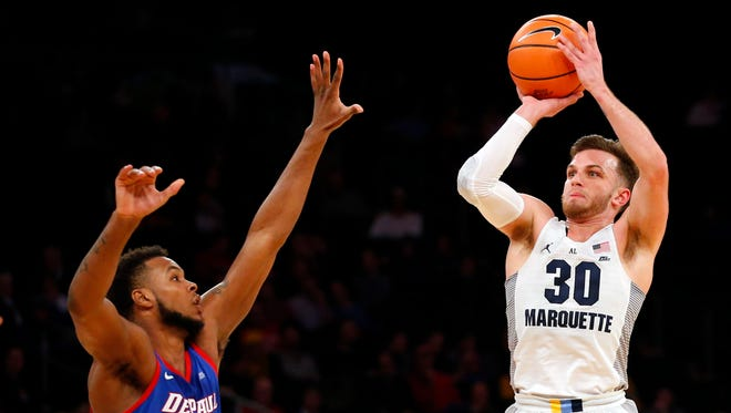 Marquette guard Andrew Rowsey shoots over DePaul forward Tre'Darius McCallum during the first  half on Wednesday.