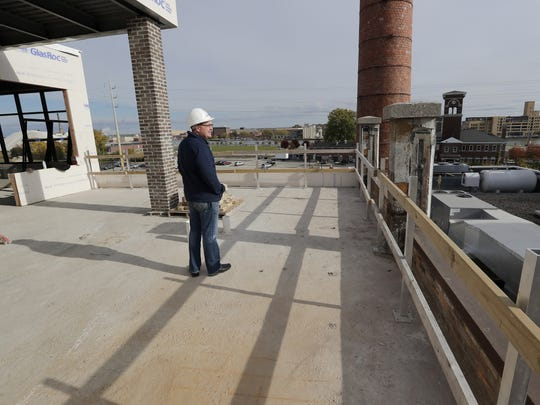 Jim Kratowicz, COO of Titletown Brewing Co., looks out from one of the newly installed balconies of the fourth floor office space being built at the former Larsen Green property.