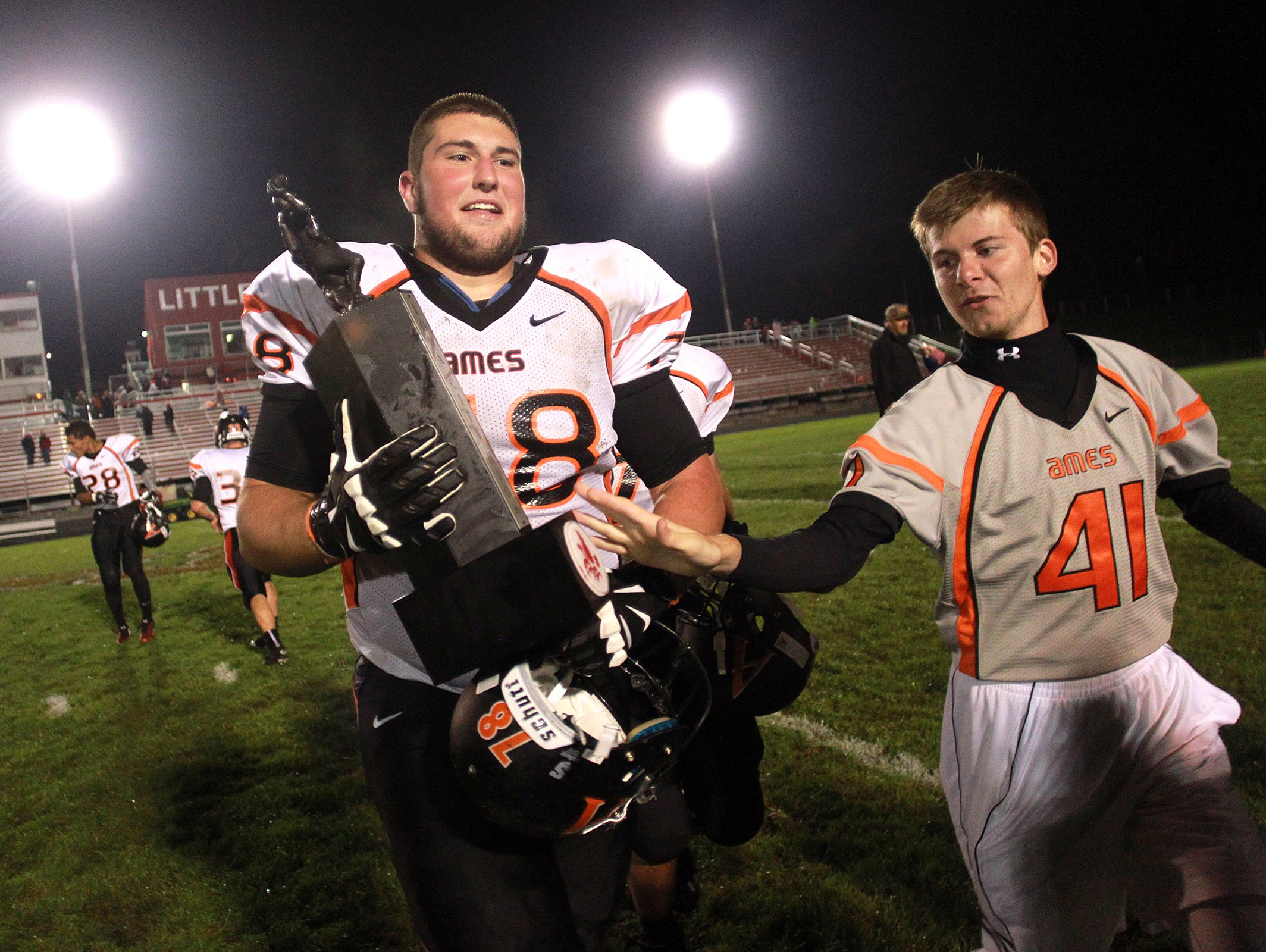 Ames' Michael Holtzbauer carries the Little Cy-Little Hawk trophy to fans following the Little Cyclones' 44-20 win at City High on Friday, Sept. 12, 2014. David Scrivner / Iowa City Press-Citizen