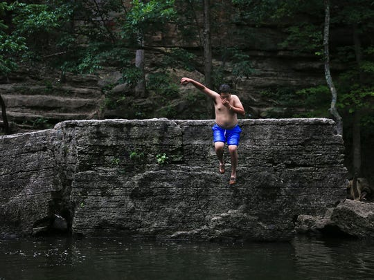 Holding his nose for good measure, 17-year-old David Jarqui takes a leap from Big Rock into Beargrass Creek while cooling off from the muggy temperature at Cherokee Park Friday afternoon. Weekend temperatures were to be around 92 degrees.