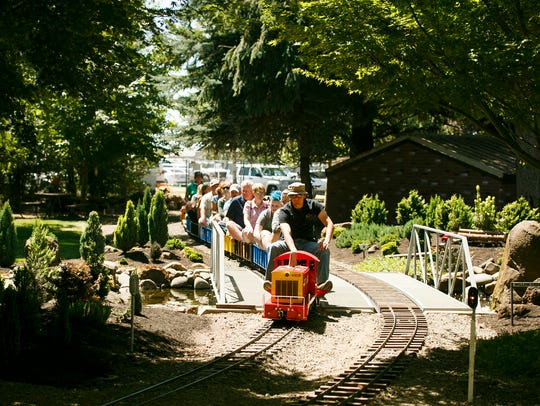 Families ride a 1/8-scale model a train at the 46th