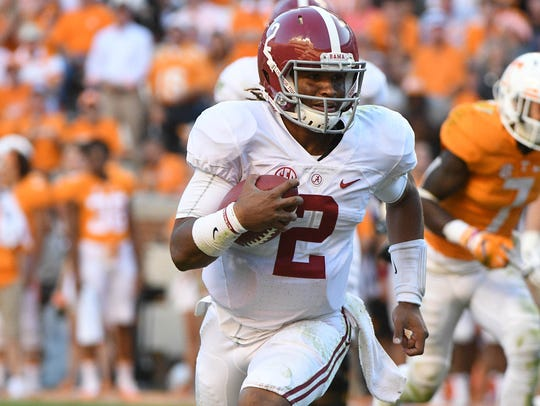 Alabama quarterback Jalen Hurts runs the  ball against
