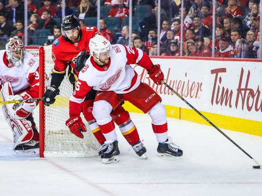Red Wings defenseman Mike Green (25) and Flames right wing Michael Frolik (67) battle for the puck in front of Red Wings goalie Petr Mrazek (34) during the third period of the Wings' 6-3 loss on Thursday, Nov. 9, 2017, in Calgary, Alberta.