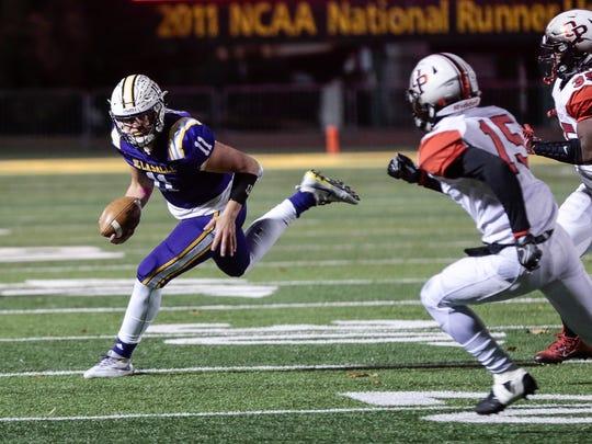 Warren De La Salle quarterback Luke Pfromm (11) keeps the ball during the MHSAA Division 2 regional final game against Oak Park at Wayne State University's Adams Field in Detroit, Friday, November 10, 2017.