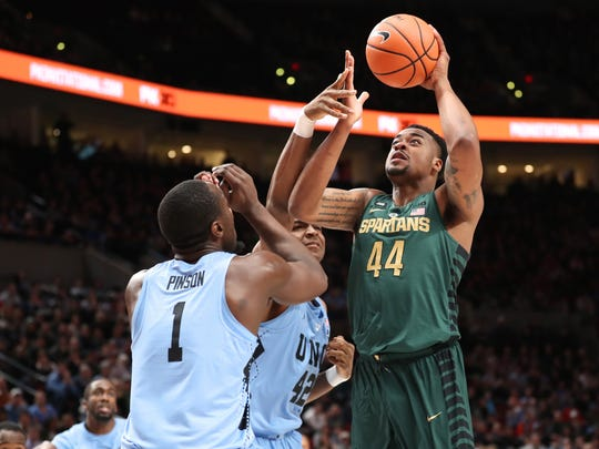 Michigan State forward Nick Ward (44) shoots over North Carolina forward Theo Pinson (1) and forward Brandon Huffman (42) in the first half in the Phil Knight Invitational tournament in Portland, Ore., Sunday, Nov. 26, 2017.