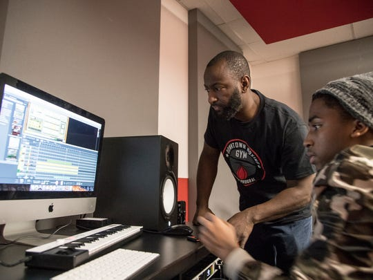 Khali Sweeney, founder and CEO of Downtown Boxing Gym, center, checks out some new beats made by Dorian Hogan, 17, right, also known as KYZ, at the Downtown Boxing Gym in Detroit, Friday, December 8, 2017.
