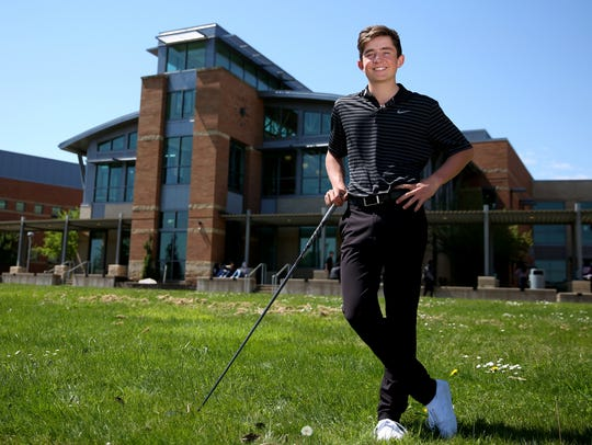Brandon Eyre, a freshman golfer, stands for a photo