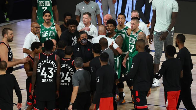 Celtics guard Marcus Smart, center, has some words for Toronto Raptors players after their double-overtime playoff game Wednesday night in Lake Buena Vista, Fla.