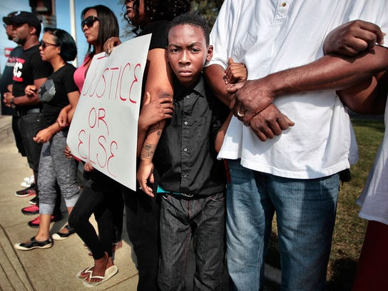 Isaiah Simpson, 10, links arms with a group of about 40 demonstrators for a few minutes of silence during a Black Lives Matter rally Aug. 9, 2015, at the corner of Winchester and Hickory Hill, where a Memphis police officer shot Darrius Stewart, a 19-year-old unarmed black man.