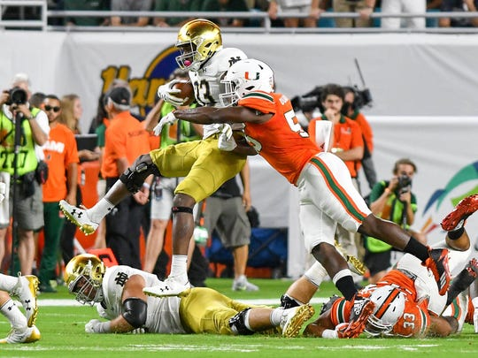 Nov 11, 2017; Miami Gardens, FL, USA; Notre Dame Fighting Irish running back Josh Adams (33) is hit by Miami Hurricanes linebacker Shaquille Quarterman (55) in the first quarter at Hard Rock Stadium. Mandatory Credit: Matt Cashore-USA TODAY Sports