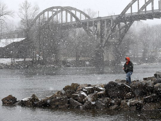 Hunter Queen, 19, of Mountain Home, fishes the White River in Cotter on Wednesday. The dedicated angler said he fishes any time he gets a chance, even if it's snowing.