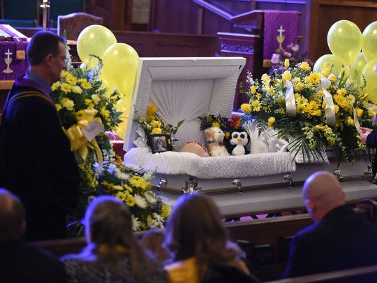 Yellow balloons and yellow flowers surround 12-year-old Auston K. Snyder's casket on Saturday. Inside sat several stuffed animals and photograph of his dog.