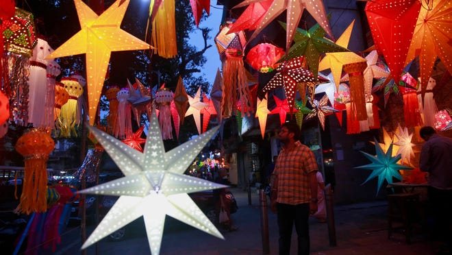 An Indian man stands near lanterns on display at a roadside stall on the eve of Diwali, the Hindu festival of lights, in Mumbai, India, Tuesday, Nov. 10, 2015. Hindus light up their homes and pray to Lakshmi, the goddess of wealth, during the festival which will be celebrated on Wednesday/AP photo/Rafiq Maqbool