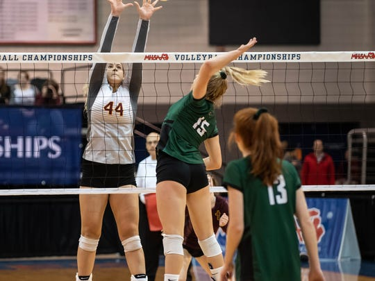 Farmington Hills Mercy's Ella Loussia (44) drills one over the Lake Orion's Sydney Smith (15) during MHSAA Volleyball semifinals at Kellogg Arena in Battle Creek.