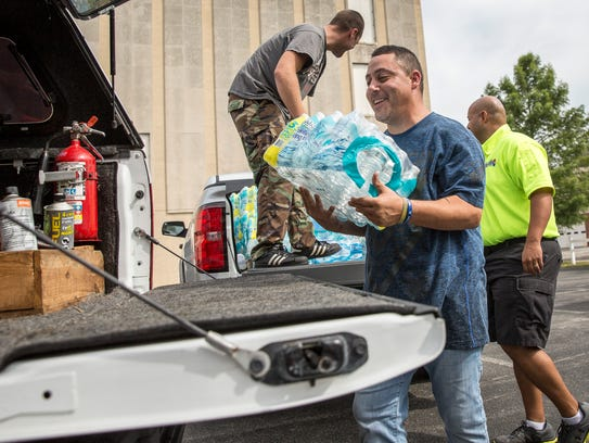 Volunteers pack a vehicle full of supplies to go down