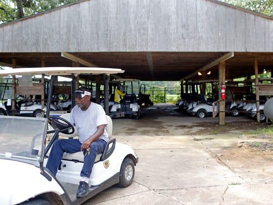 A Grove Park Golf Course employee retrieves a golf