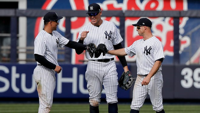 New York Yankees outfielders, from left, Jace Peterson, Aaron Judge and Brett Gardner (11) celebrate after the Yankees beat the Baltimore Orioles 8-3 in a baseball game, Saturday, April 7, 2018, in New York.