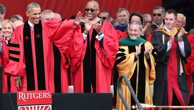In this Sunday, May 15 photo, Rutgers student government president Matthew Panconi, front right, applauds as President Barack Obama, left, waves to the crowd at the Rutgers graduation ceremonies Sunday, in Piscataway, N.J. Dianne Totten, Panconi's 70-year-old grandmother, who helped Rutgers University nab President Barack Obama as its commencement speaker says she hasn't stopped smiling about that special day.