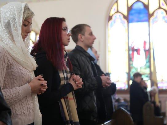 Tatyana L. and her sister, Viktoriya Grabobetska, are shown at St. Mary Protectress Ukrainian Orthodox Church during the divine liturgy, Sunday, Jan. 7, 2018.