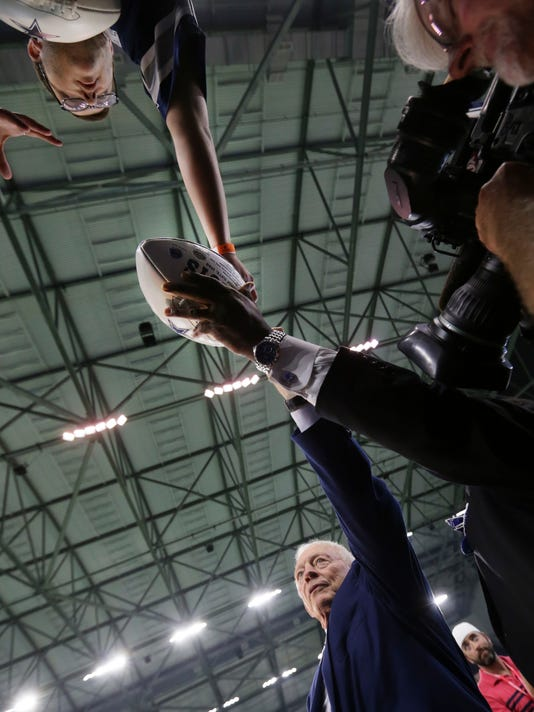 Dallas Cowboys owner Jerry Jones, bottom right, takes a football to sing an autograph for a fan before the start of an NFL training camp football practice at the team's headquarters in Frisco, Texas, Monday, Aug. 21, 2017. (AP Photo/LM Otero)