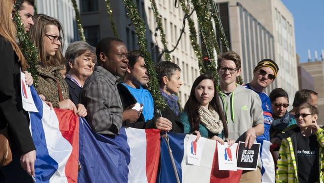 Jean Minka, president of the Alliance Française d'Indianapolis, spoke at an anti-terror rally on Saturday, Nov. 14, 2015, on Monument Circle in Downtown Indianapolis..