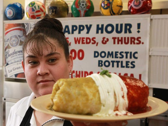 March 24, 2010: Server Angilica Espinoza holds up a Fried burrito at La Mexicana restaurant.