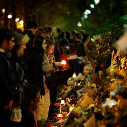 A woman lights a candle outside the Bataclan concert